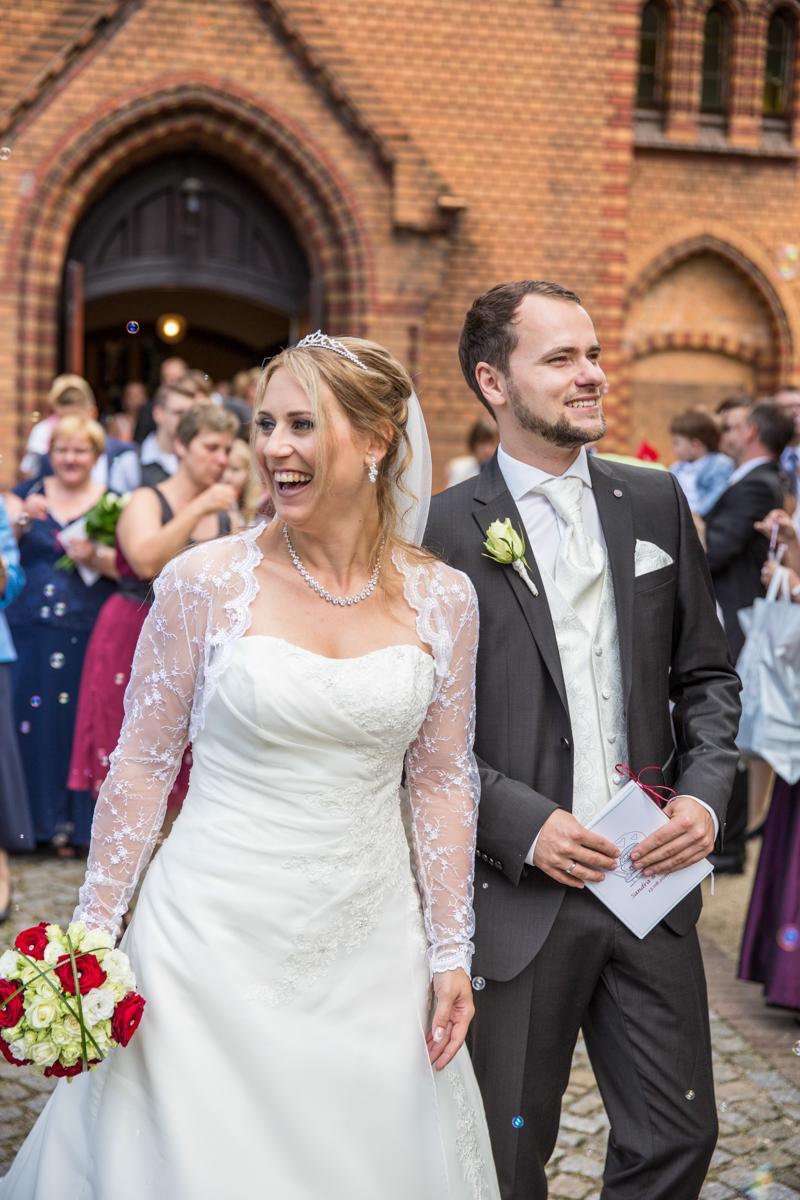 Braut und Bräutigam nach der Trauung vor der Kirche