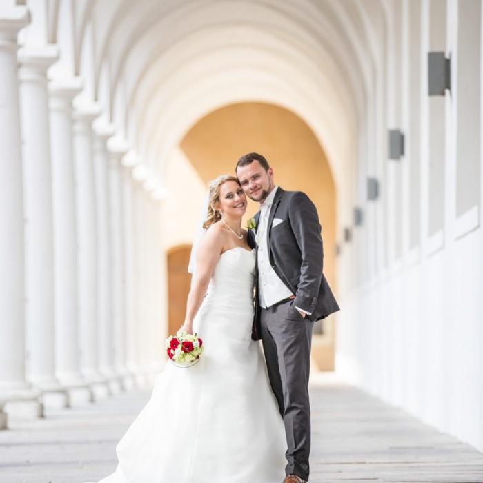 Hochzeitspaar vor Gang aus weißen Säulen