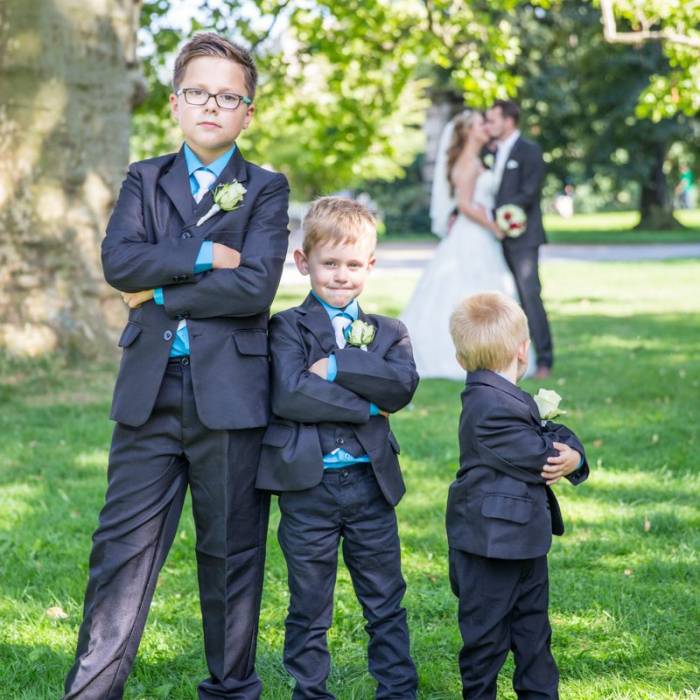 Drei Kinder im Anzug, einer der drei dreht sich zu den küssenden Eltern um