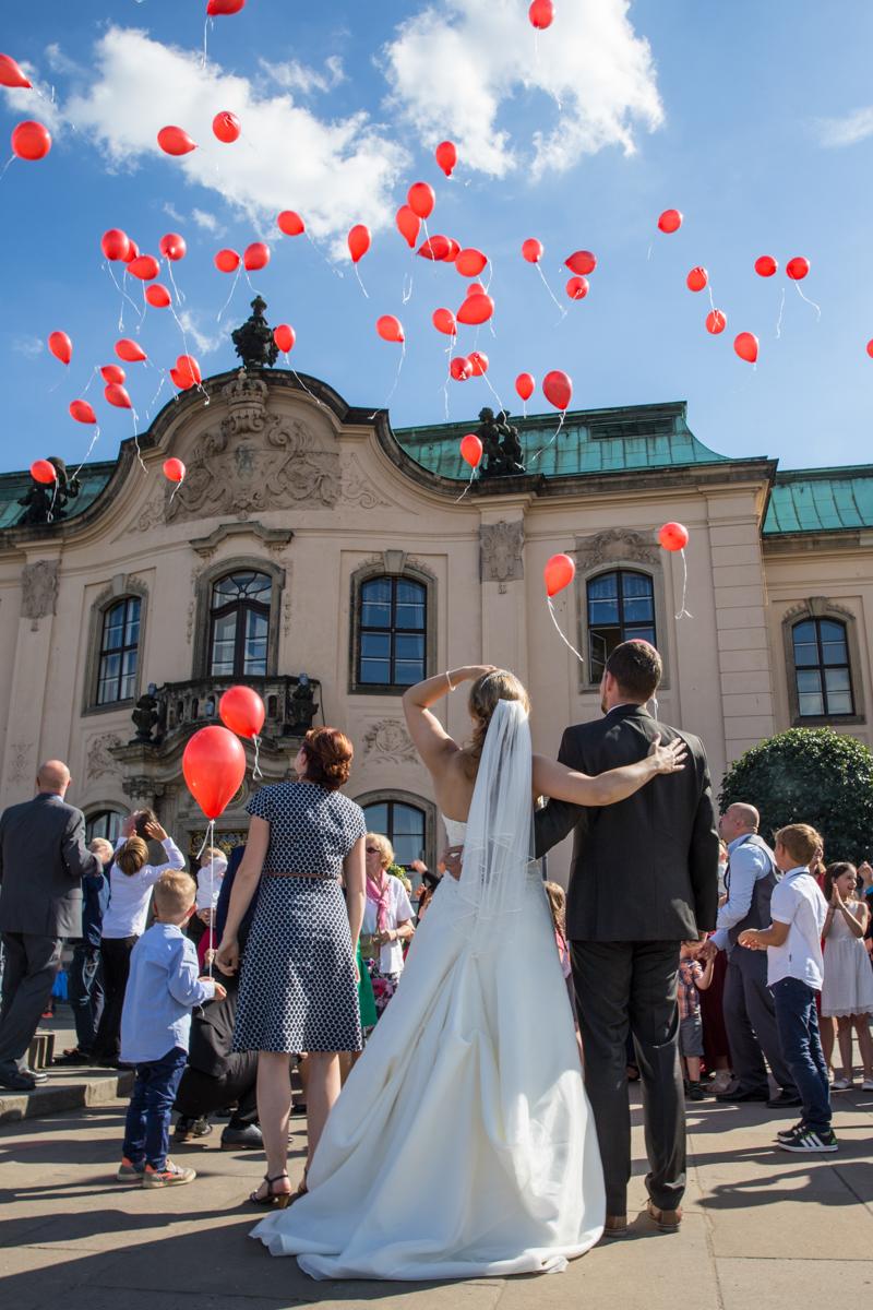Hochzeitsgesellschaft lässt rote Luftballons in den Himmel steigen