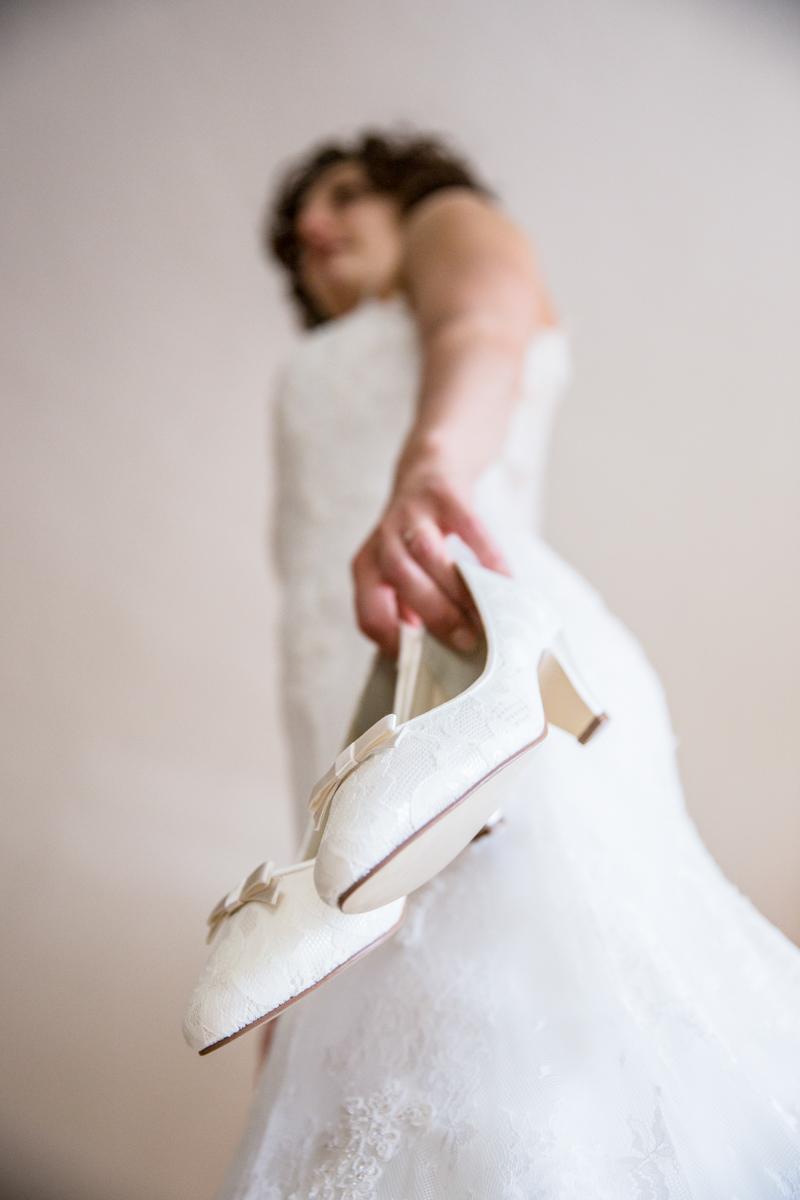 Braut hält Hochzeitsschuhe in der Hand