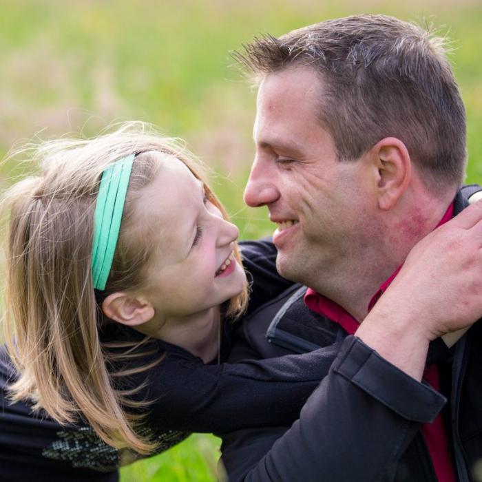 Vater und Tochter umarmen sich auf Blumenwiese