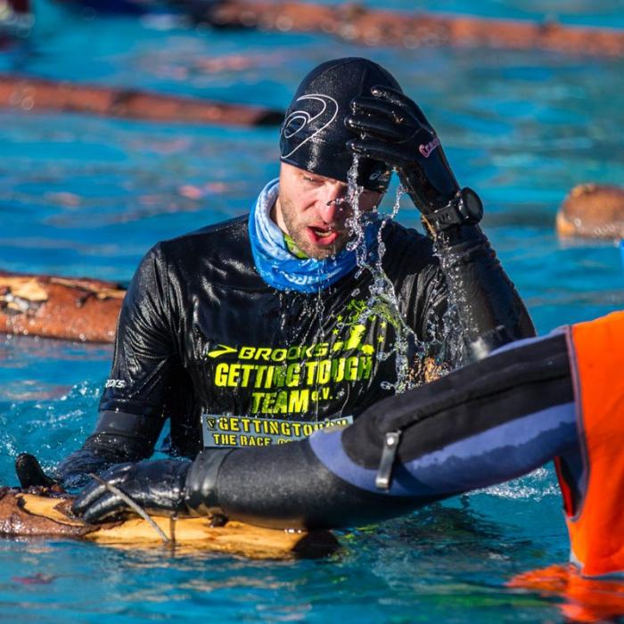 OCR-Athlet überwindet Tauchhindernis im Winter