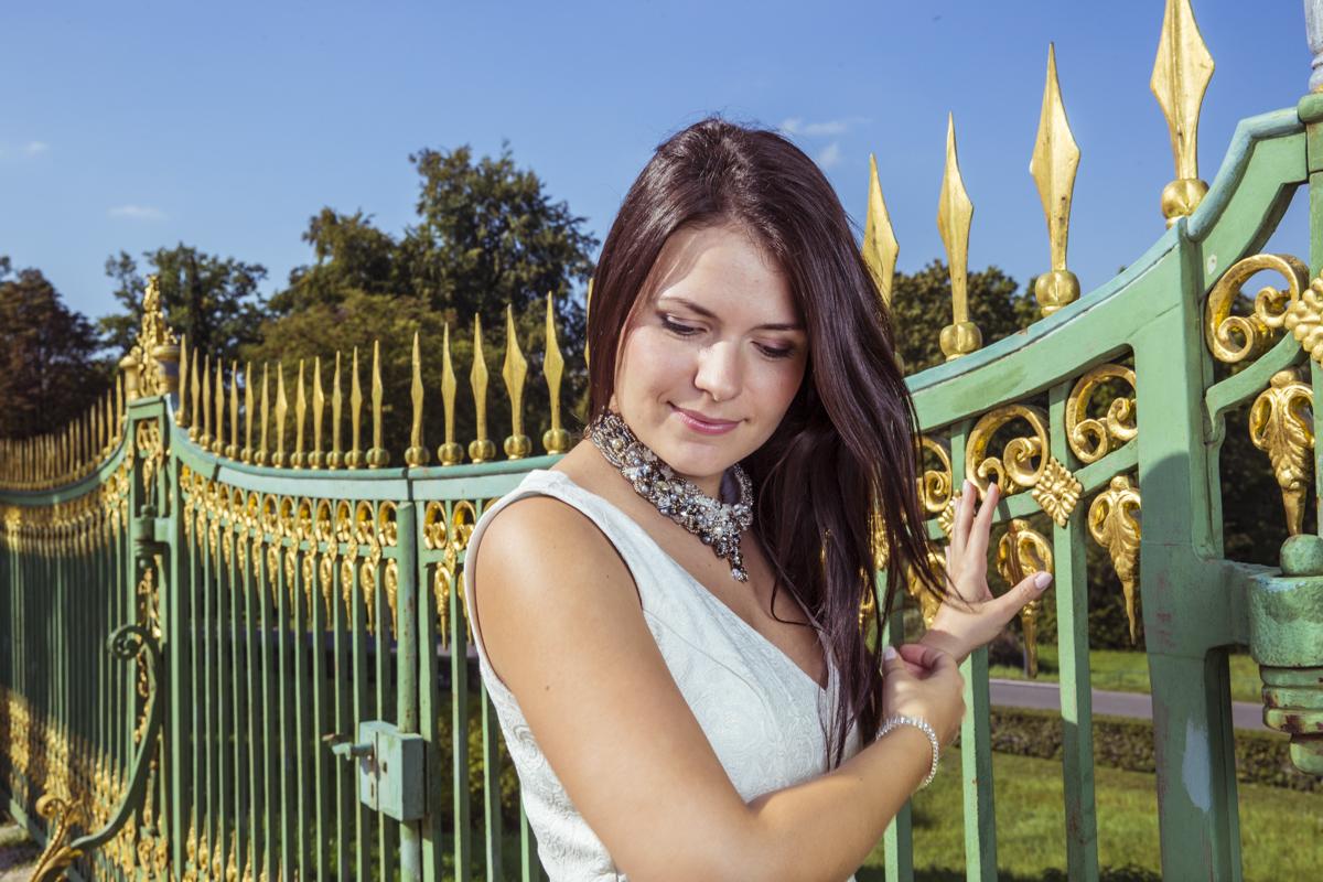 Mädchen an goldverziertem Zaun