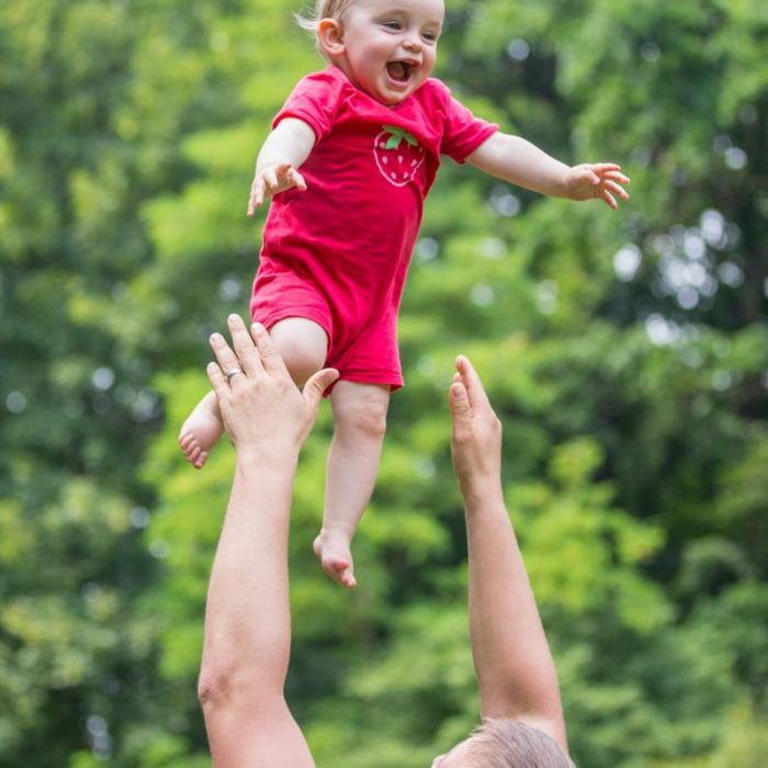 Vater wirft lachende Tochter in die Höhe