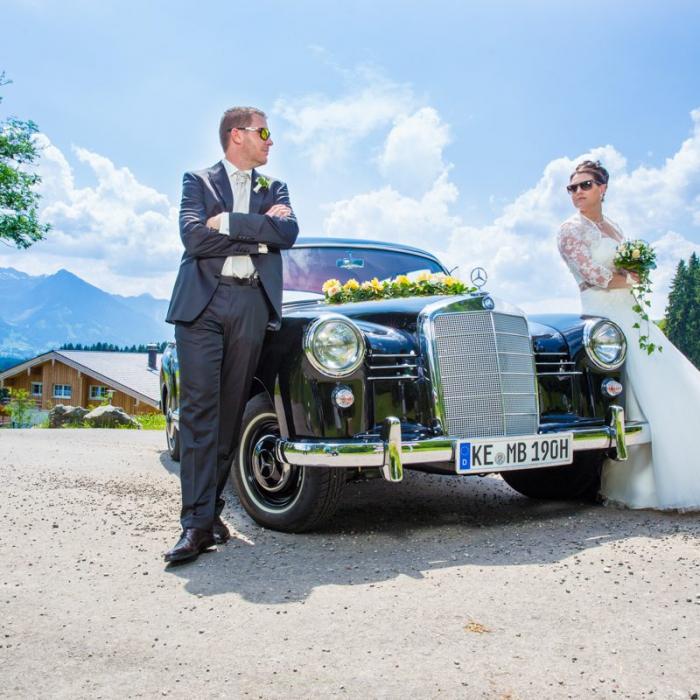 Hochzeitspaar lehnt an Oldtimer