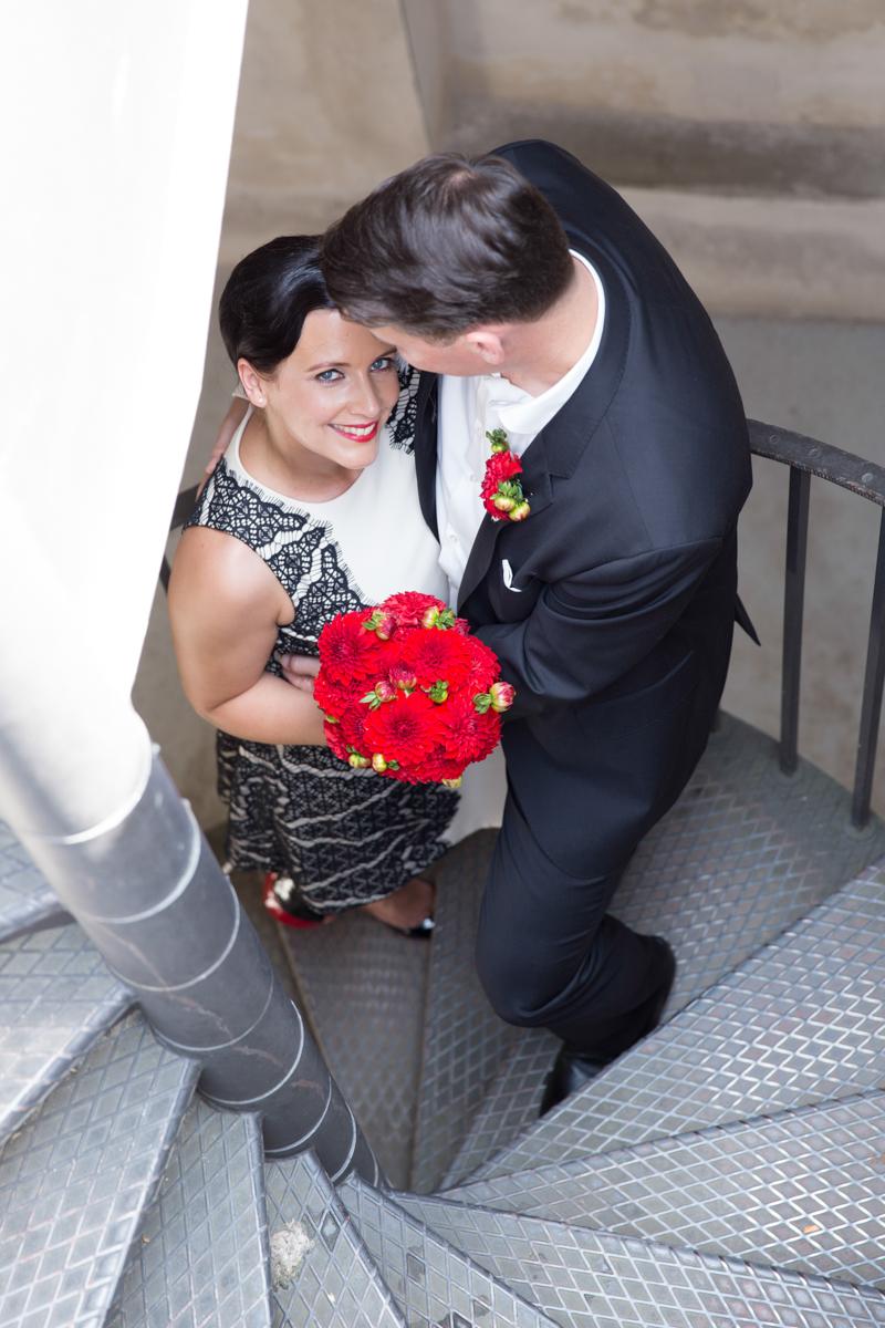 Paar mit Hochzeitsstrauß auf Wendeltreppe