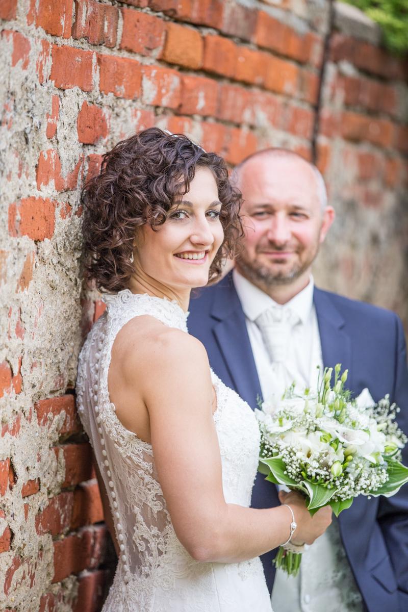 Hochzeitspaar vor Ziegelwand