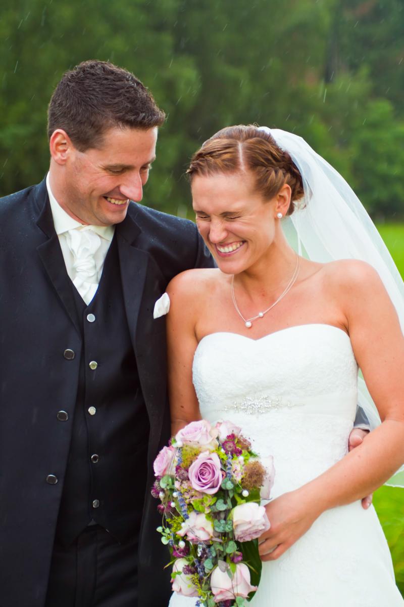 Hochzeitspaar lachend im Regen