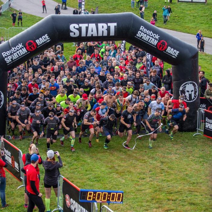 Läufer starten unter dem Startbogen in einen Wettkampf