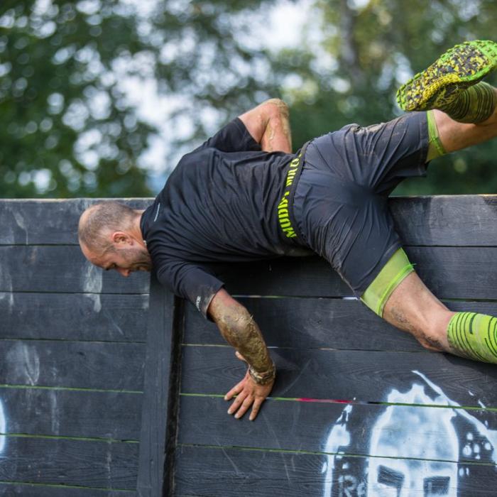 Sportler springt über eine Hinderniswand
